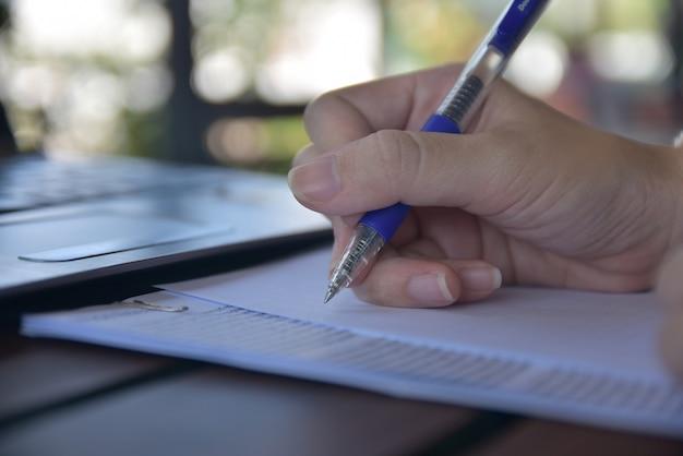 Pessoa escrevendo em papéis
