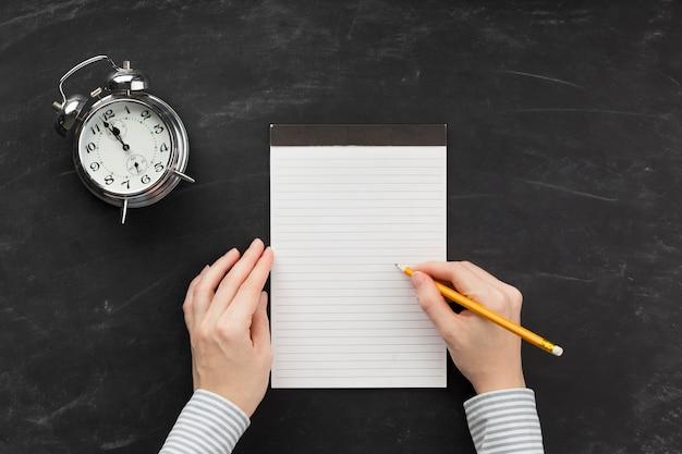 Pessoa escrevendo em um bloco de notas vazio