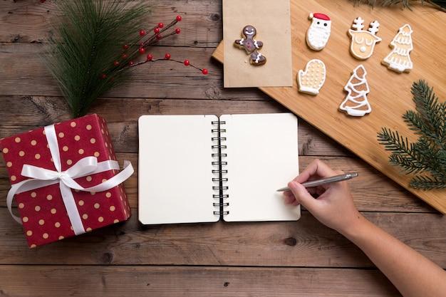 Pessoa, escrevendo no caderno aberto com caixa de presente e saborosos biscoitos caseiros de natal