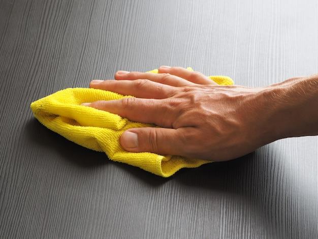Pessoa esfrega uma mesa com um pano de microfibra