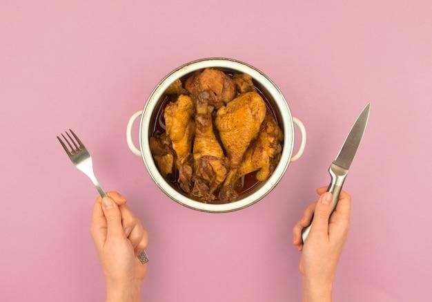 Pessoa faminta com um homem com garfo e faca pronto para comer frango assado em uma panela, conceito de fome infantil, foto da vista superior