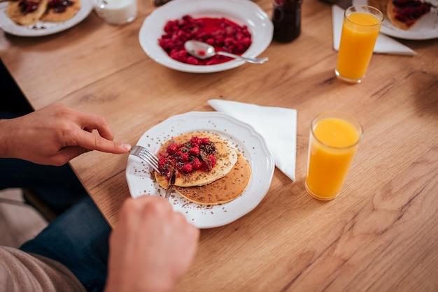 Pessoa fatiar e comer saborosas panquecas com framboesas na mesa de madeira.