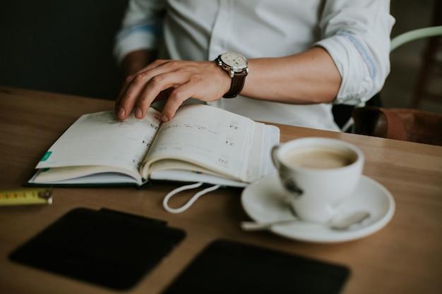Pessoa fazendo anotações em um caderno enquanto trabalha em casa