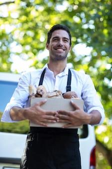 Pessoa feliz entrega carregando pacote de comida