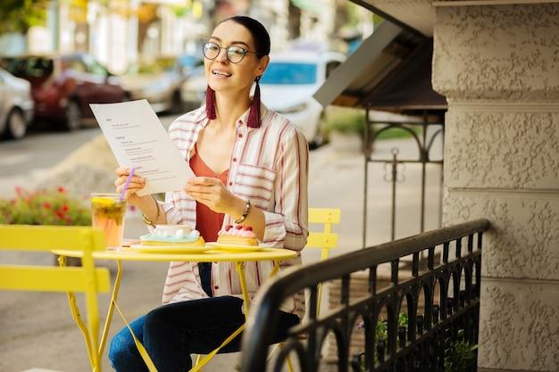 Pessoa feliz. jovem alegre aproveitando a hora do almoço e sorrindo enquanto está sentada ao ar livre com um menu nas mãos