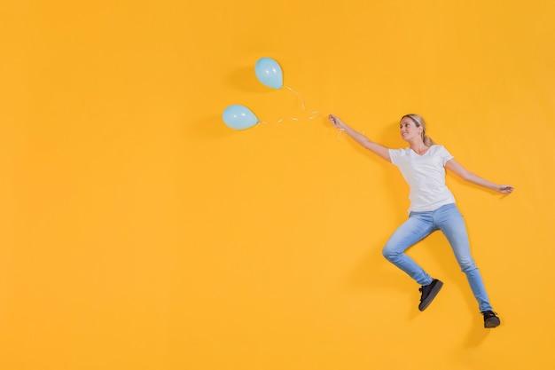 Pessoa flutuando com balões azuis