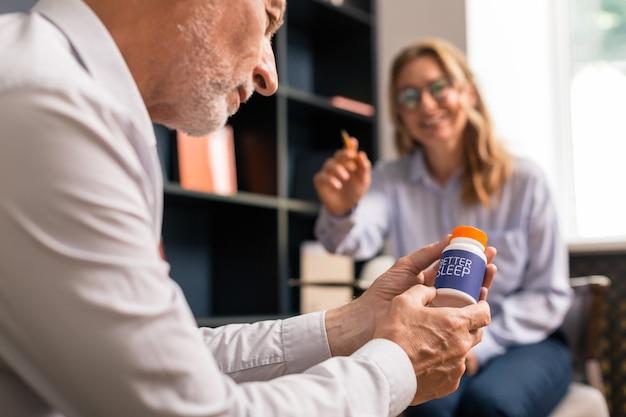 Pessoa focada. closeup retrato de um homem concentrado olhando para uma caixa de pílulas para dormir nas mãos enquanto está sentado na frente de uma mulher sorridente durante a sessão de terapia