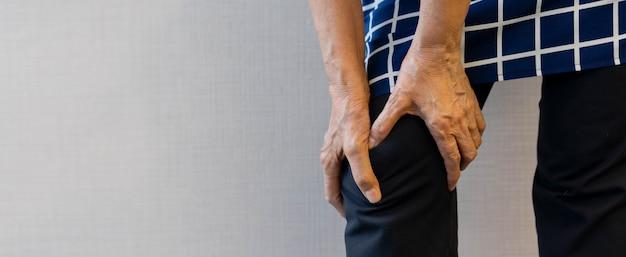 Pessoa idosa madura, fazendo massagem nas mãos no joelho