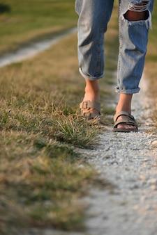 Pessoa irreconhecível caminhando pela estrada rural