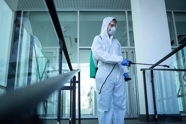 Pessoa irreconhecível em traje de proteção branco, desinfetando áreas públicas para impedir a disseminação do vírus corona altamente contagioso