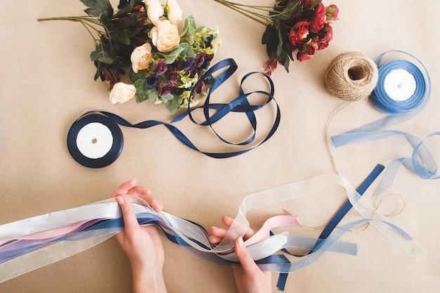 Pessoa irreconhecível fazendo decorações com fitas e flores artificiais coloridas