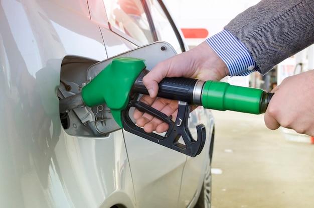 Pessoa irreconhecível reabastecendo o carro no posto de gasolina.