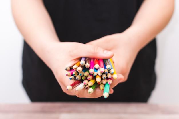 Pessoa irreconhecível, segurando o lápis de cor