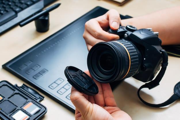 Pessoa irreconhecível segurando uma câmera e remove a tampa da lente em seu local de trabalho