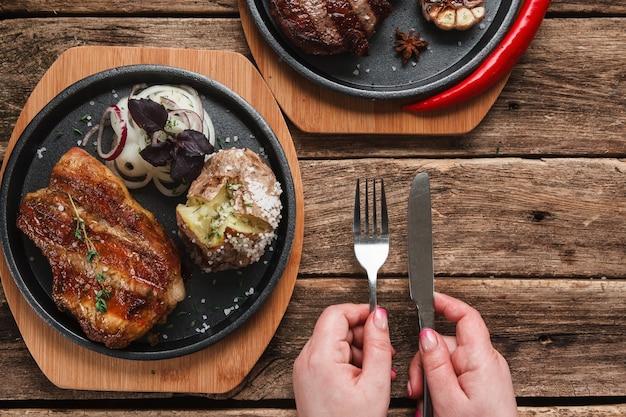 Pessoa irreconhecível tendo refeição de estaca de beaf superior com batata cozida e anéis de cebola, vista superior.