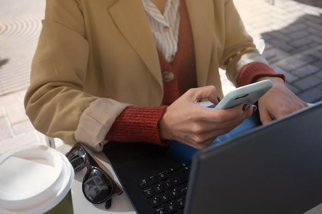 Pessoa irreconhecível trabalhando com computador e celular fora de uma cafeteria, conceito nômade digital.