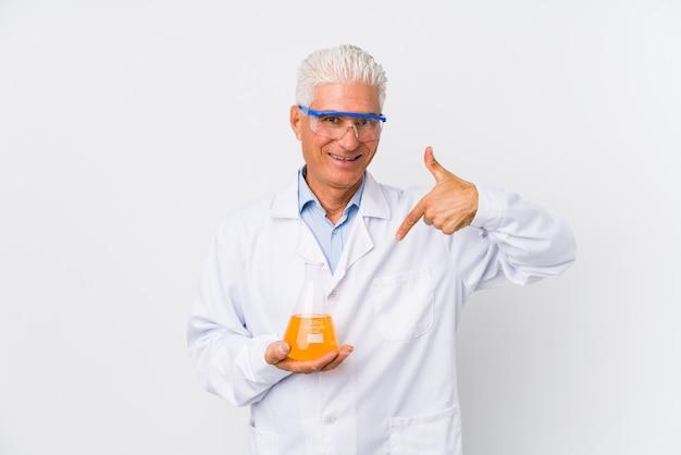 Pessoa isolada de homem químico maduro, apontando à mão para um espaço de cópia de camisa, orgulhoso e confiante