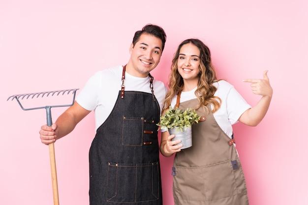 Pessoa isolada do jovem jardineiro casal apontando à mão para um espaço de cópia de camisa, orgulhoso e confiante