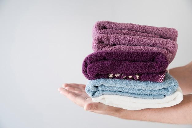 Pessoa lateral segurando toalhas empilhadas