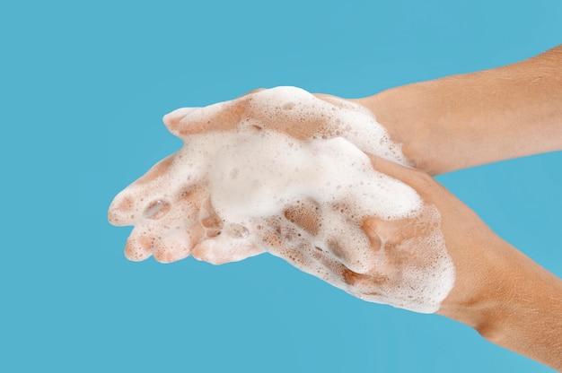 Pessoa lavando as mãos com fundo azul