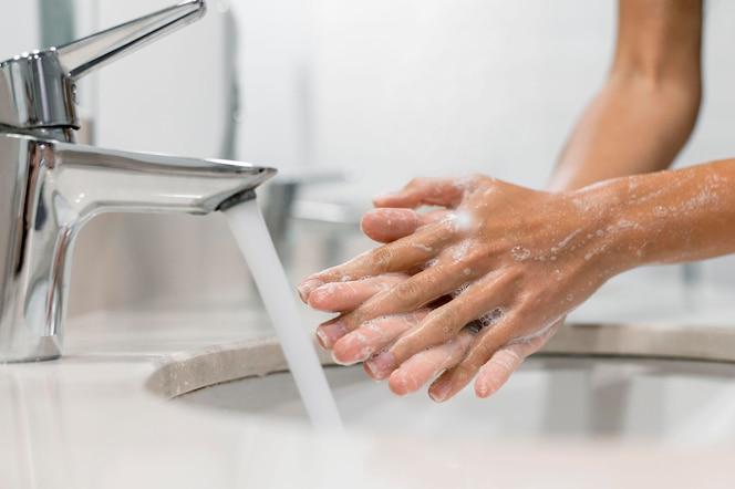 Pessoa lavando as mãos com sabão