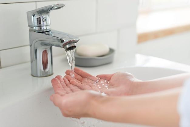 Pessoa, lavando as mãos na pia com água
