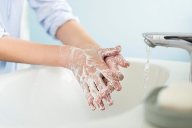 Pessoa lavando as mãos no banheiro
