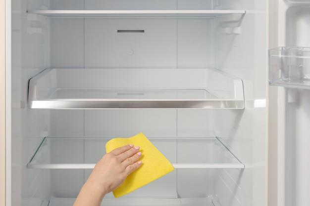 Pessoa lavando geladeira com pano.