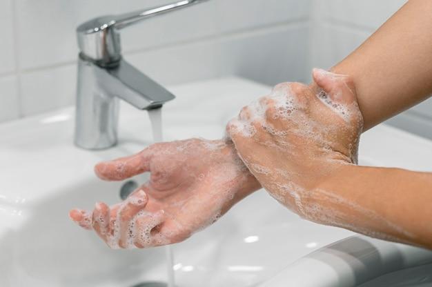 Pessoa lavando o pulso com sabonete