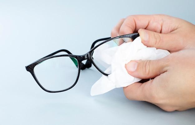 Pessoa limpando óculos pretos com lenços especiais
