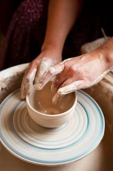 Pessoa modelando em argila em uma roda de oleiro