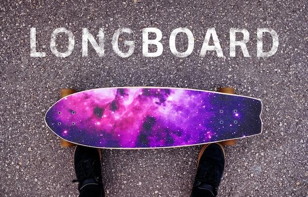 Pessoa na frente de seu longboard ao lado de um texto: longboard
