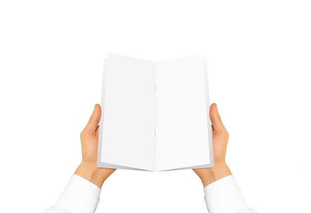 Pessoa na manga da camisa branca, segurando o livro em branco