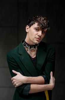 Pessoa não binária em jaqueta verde posando de forma artística