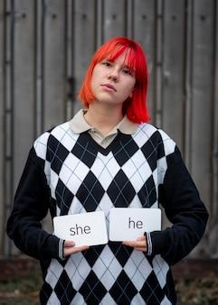 Pessoa não binária segurando cartas de pronomes