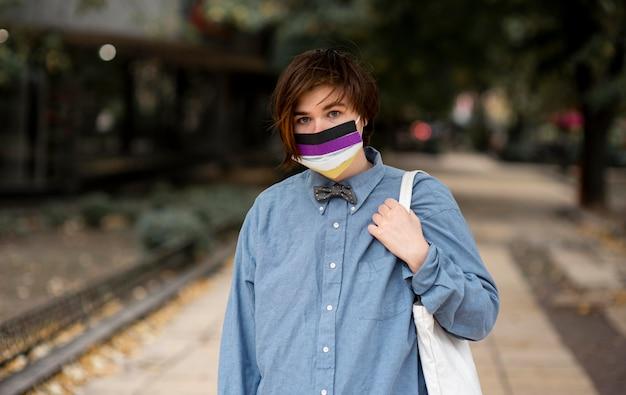 Pessoa não binária usando máscara médica com bandeira representativa