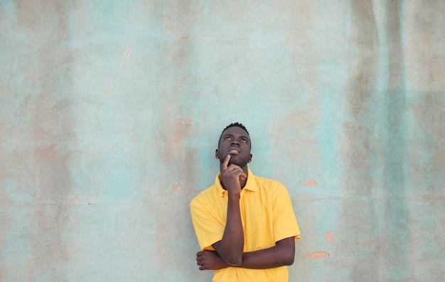Pessoa negra mostrando hesitação e dúvida atrás de uma parede