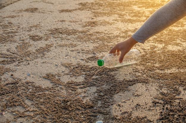 Pessoa pegando garrafa de plástico de limpeza na praia
