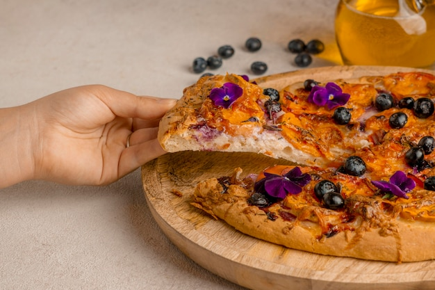 Pessoa pegando uma fatia de pizza com mirtilos e pétalas de flores