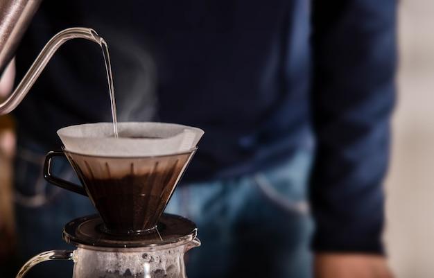 Pessoa pingando café em casa pela manhã.