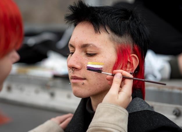 Pessoa pintando uma bandeira não binária no close-up de um amigo