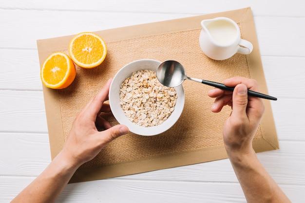 Pessoa que come aveia; laranja e leite cortados ao meio no placemat da juta sobre a superfície branca