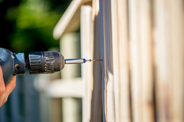 Pessoa que constrói uma cerca de madeira com uma furadeira e parafuso usando uma furadeira portátil em um conceito de manutenção de quintal, reformas e bricolage.