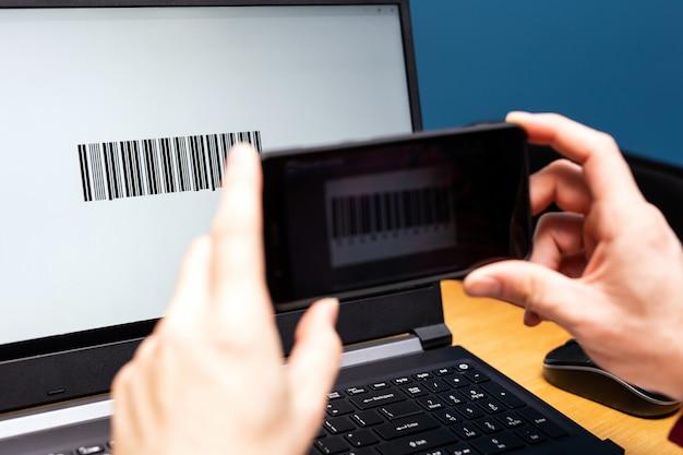 Pessoa que digitaliza com telefone celular, código de barras na tela do computador, pagamento moderno on-line com smartphone de aplicativo de digitalização
