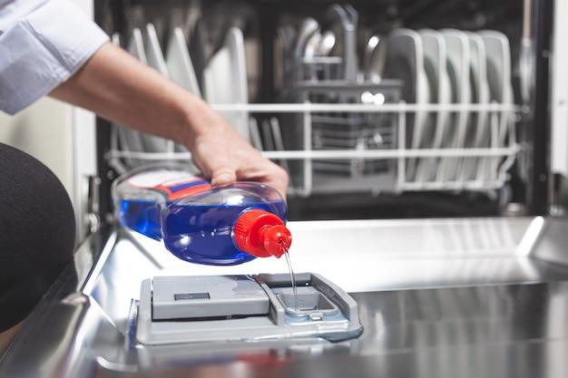 Pessoa que enche a máquina de lavar louça com líquido brilhante na caixa da máquina de lavar louça