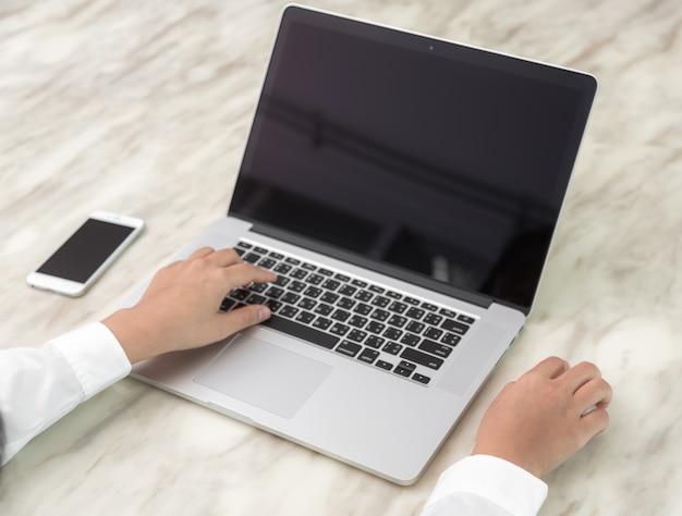 Pessoa que escreve com uma mão ea outra tocando um mouse