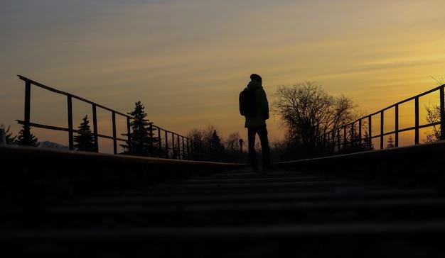 Pessoa que está no meio dos trilhos antigos de um trem ao pôr do sol.