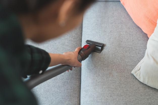 Pessoa que faz trabalhos domésticos e limpeza do sofá.