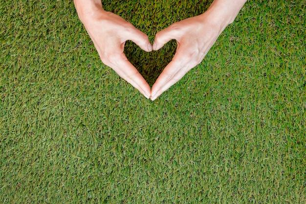 Pessoa que faz um coração com as mãos na grama, com espaço de cópia