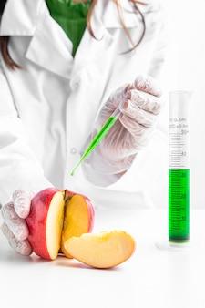 Pessoa que injeta uma maçã com produtos químicos verdes